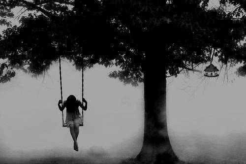 black and white image of a woman swinging from a tree